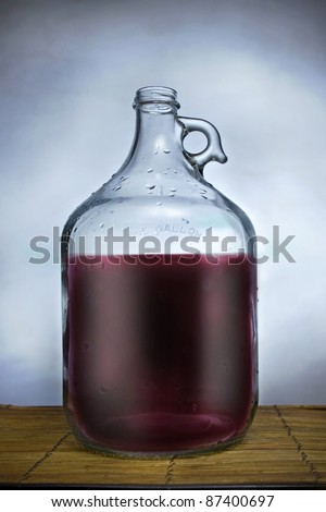 One gallon glass jug filled with wine, set on a table with blue background - stock photo