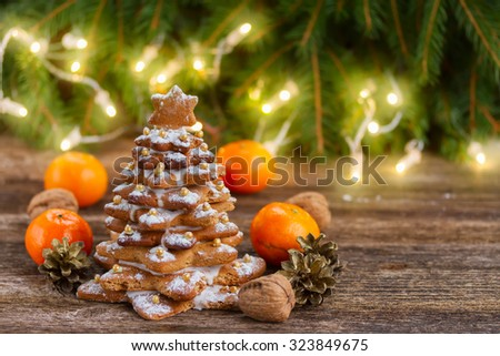 one gingerbread  tree with tabgerines and christmas lights in background - stock photo