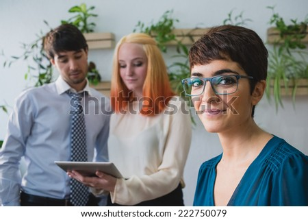 One girl focused looking at camera and two partners behind - stock photo