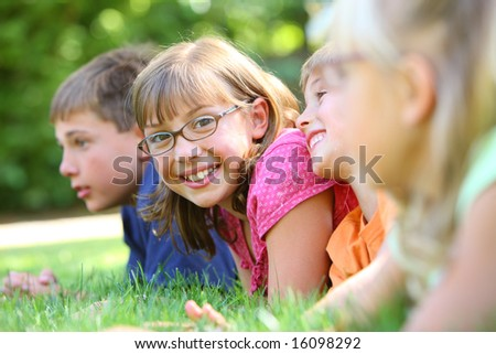 One girl looking at camera in group of kids - stock photo