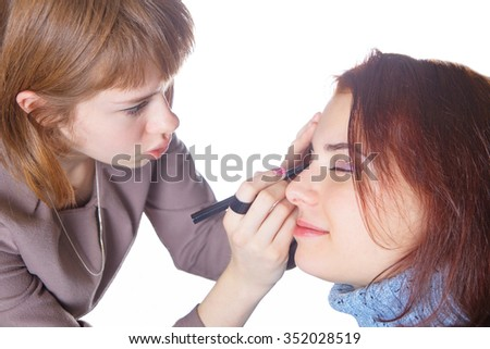 One girl makes the other girl make-up on white background.