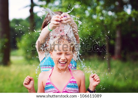 one girl splashing a water balloon to another girl - stock photo