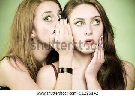 One girl whispering to other some news. Surprised face and palm near face in second girl. Image in green spring colors - stock photo