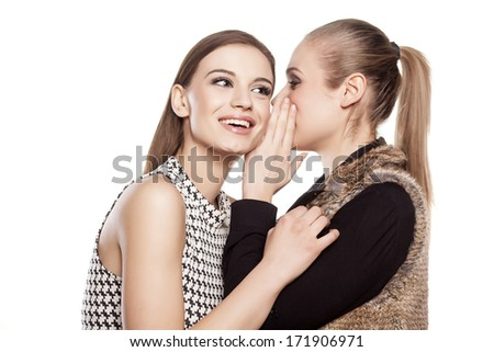 one girl whispers good news to another girl - stock photo