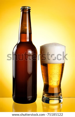 One glass and Bottle of fresh light beer on yellow background - stock photo