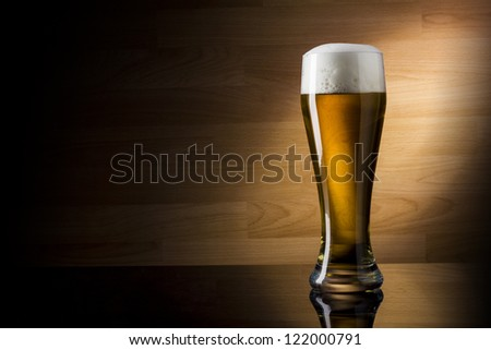 One glass beer on wood background with copyspace