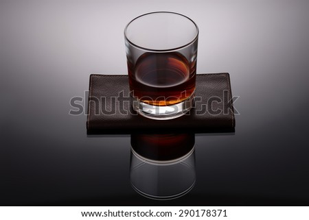 One glass cup with strong amber alcoholic drink reflecting and standing on brown leather napkin on grey and white background, horizontal picture - stock photo
