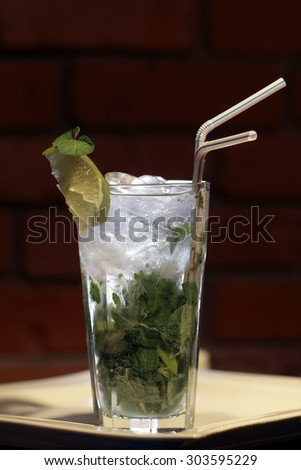 One glass goblet with alcoholic mojito cocktail of light cuban rum fresh lime juice fresh mint leaves granulated sugar soda water and ice cubes and drink straw on brick background, vertical photo - stock photo