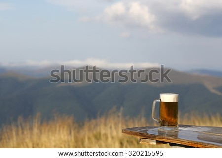 One glass mug with lager or porter tasty frothy beer on wooden table top sunny day outdoor on natural with mountain hills and yellow dry grass and cloudy sky background copyspace, horizontal picture - stock photo