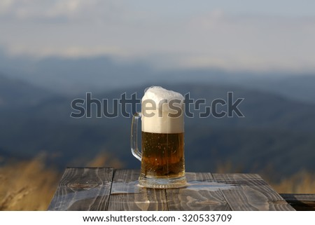 One glass mug with lager or porter tasty frothy beer on wooden table top sunny day outdoor on natural with mountain hills and yellow dry grass background, horizontal picture - stock photo