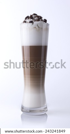 One glass of delicious fresh layered latte macchiato coffee with cream and coffee beans and cocoa powder on top, on a white reflecting board - stock photo