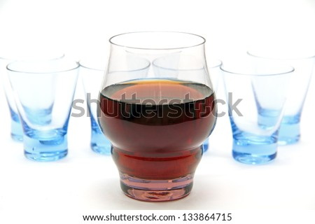 one glass of wine with a drink and a few empty glasses for vodka. - stock photo