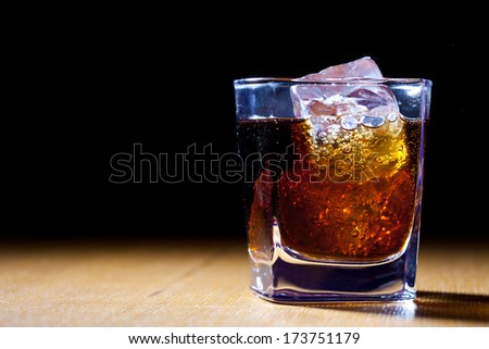 one glass with a drink and ice, close up