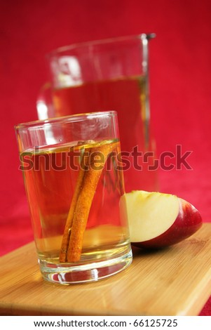 One glass with apple juice and cinnamon stick with a pitcher in background