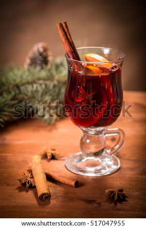One glass with mulled wine with Christmas background