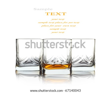 One glass with whiskey and two empty glass over white background - stock photo