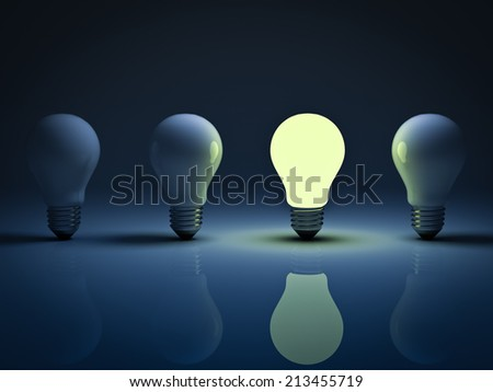 One glowing light bulb standing amongst the unlit incandescent bulbs with reflection , the different concept - stock photo