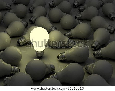 One glowing light bulb standing out from the unlit incandescent bulbs - stock photo