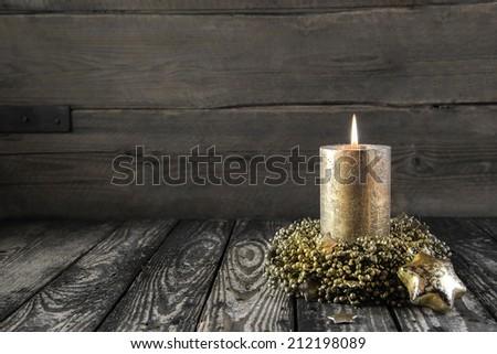 One golden burning advent candle on wooden nostalgic background. - stock photo