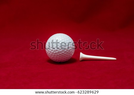 One golf ball and one pin and red flannel background