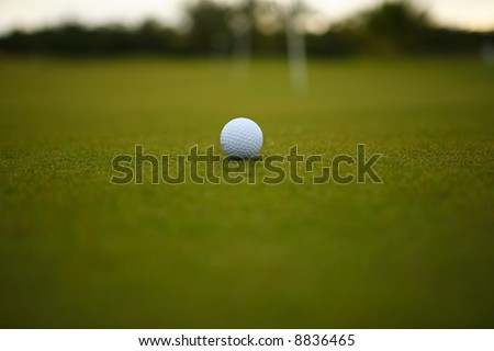 One golf ball over green grass - stock photo