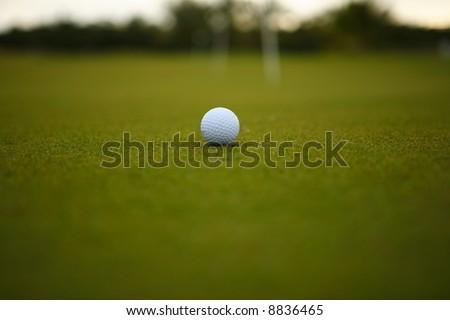 One golf ball over green grass - stock photo