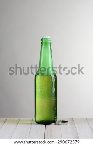 One green beer bottle on a wood table against a light to dark gray background. The bottle is open with foam coming out the open top. Vertical format with copy space. - stock photo