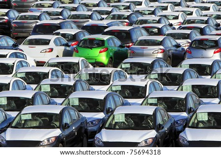 One green car among many other cars - stock photo
