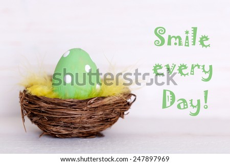 One Green Dotted Easter Eggs In Easter Basket Or Nest On White Wooden Background With Life Quote Smile Every Day Used As Easter Decoration Or Easter Greetings Vintage Or Old Fashion Style - stock photo