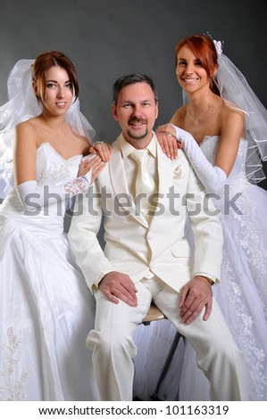 One groom and two brides - stock photo