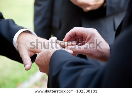 One groom placing the ring on another man's finger during gay wedding. - stock photo