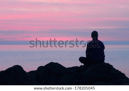 One guy sits on a rock by the sea and looking at pink sunset - stock photo