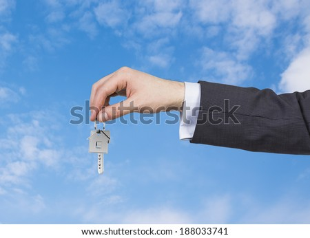 One hand and a key. Sky background.