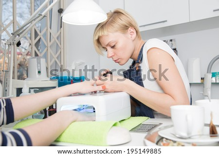 one hand dries nails in  UV lamp and  other colors manicurist - stock photo