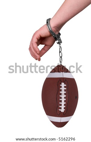 One hand handcuffed to a football isolated over white - stock photo