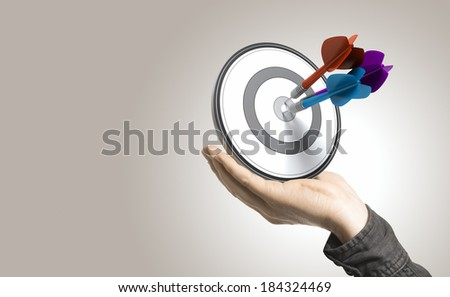 One hand holding a target with three darts hitting the center, beige background. Illustration of control and effective business solutions. - stock photo