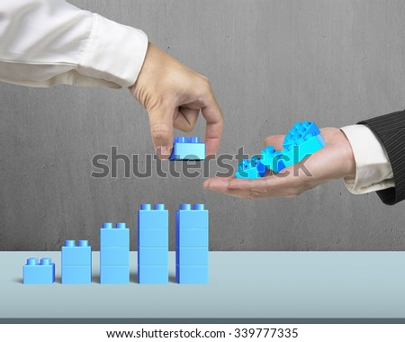 One hand holding blue stack blocks to the other hand completing growth bar graph shape on table, with concrete wall background. - stock photo