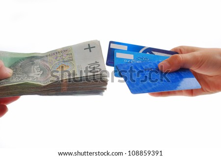 one hand holding stack of polish banknotes and second hand holding credit cards isolated on white