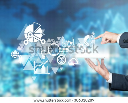 One hand is holding a tablet, other one is pointing out the projected icon. Business icons hologram in the air. City landscape in blur as a background.