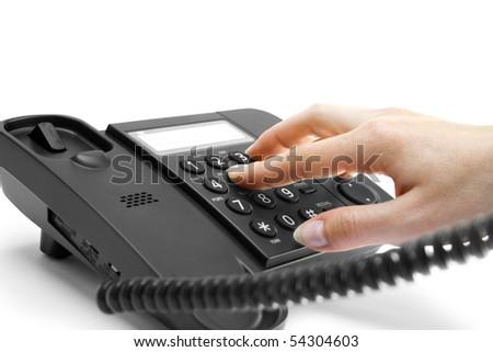 One hand pressing key on black phone - stock photo