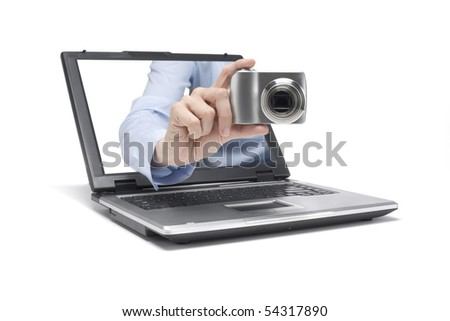 one hand reaches out of a laptop and takes a picture - stock photo