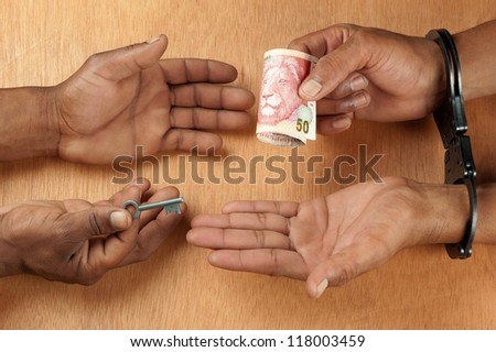 One hand receives a bribe whilst the other hand issues the  key to unlock the handcuffs worn by a person in custody. - stock photo
