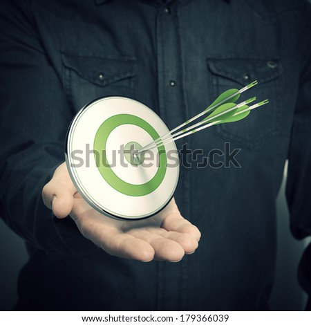one hand with a green target and three arrows, Symbol of marketing solutions or successful company advertising, blur effect. - stock photo