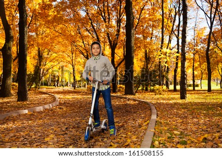 One handsome black 10 years old boy riding a scooter in autumn park with maple orange leaves wearing autumn sweatshirt with hood