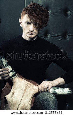 One handsome red haired young stylish unshaven man in jersey and grey trousers holding animall scull head with antlers sitting in studio on black leather background, vertical picture - stock photo
