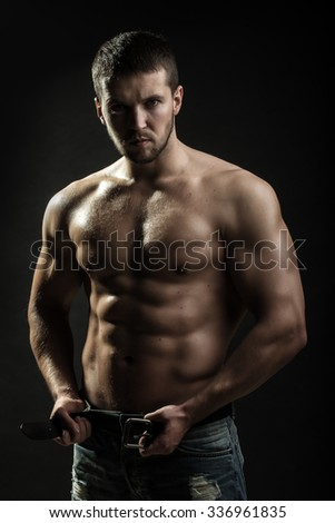 One handsome sexual strong young undressing man with muscular body in blue jeans holding hands on torso standing in studio on black background, vertical picture - stock photo