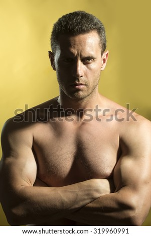 One handsome strong young naked muscular male model with beautiful straight body standing folded arms on bare chest looking forward in studio on yellow background, vertical picture