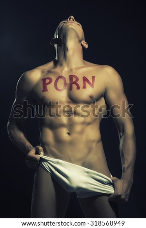 One handsome undressed muscular man in white underwear with beautiful sexy body with text of porn written by red lipstick standing with trown back head in studio on black background, vertical picture - stock photo