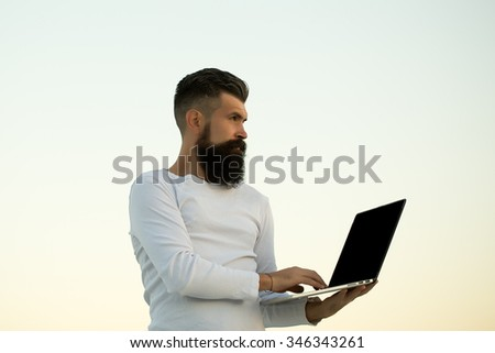 One handsome young bearded business man in white sweater holding and working on laptop outdoor on light sky natural background, horizontal picture