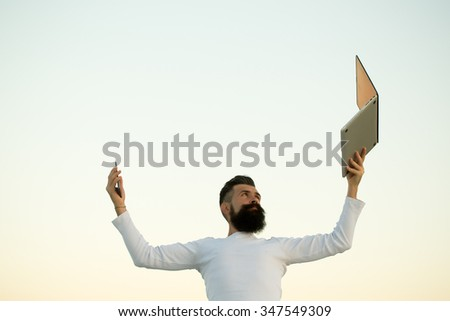 One handsome young bearded business man in white sweater holding and working on laptop with mobile phone outdoor on light sky natural background, horizontal picture - stock photo